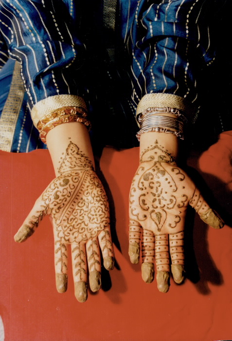 A helping hand: Nozhat Choudry Rao; second from right; applies henna stain to friends' hands as they get a head start on the three-day Islamic festival of Eid ul-Fitr. Using henna is a traditional ritual; Nozhat says.  Toronto Star Archive photograph