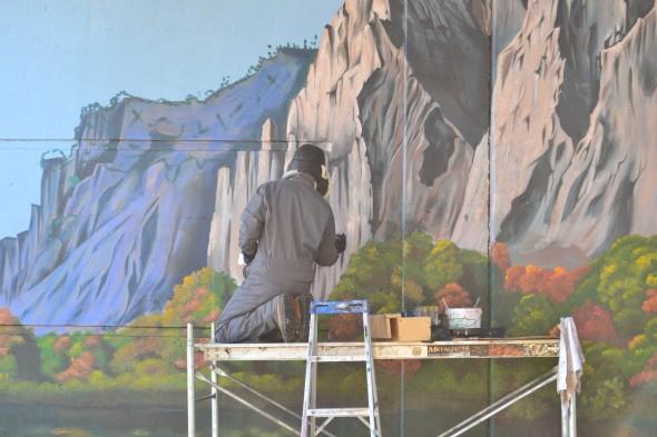 Artist Andrew Horne painting underpass mural