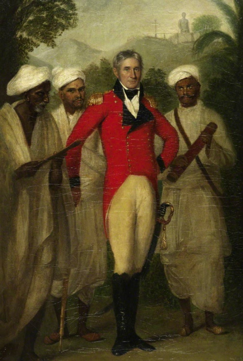Portrait of Colin Mackenzie painted by Thomas Hickey in 1816. Mackenzie, wearing scarlet uniform, is accompanied by three of his Indian assistants. In the distance is the colossal Jain statue of Gomatesvara at Karkala. British Library, Foster 13