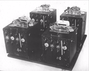 Four complex black electrical machines with dials and knobs on their fronts and rotors on top