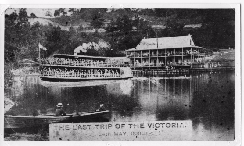 Steam boat full of passengers and a small boat on a lake