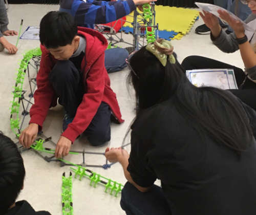 People working together to put together the K'Nex Roller Coaster.