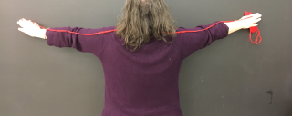 Person with out stretched arms standing against a blank wall with a length of string.
