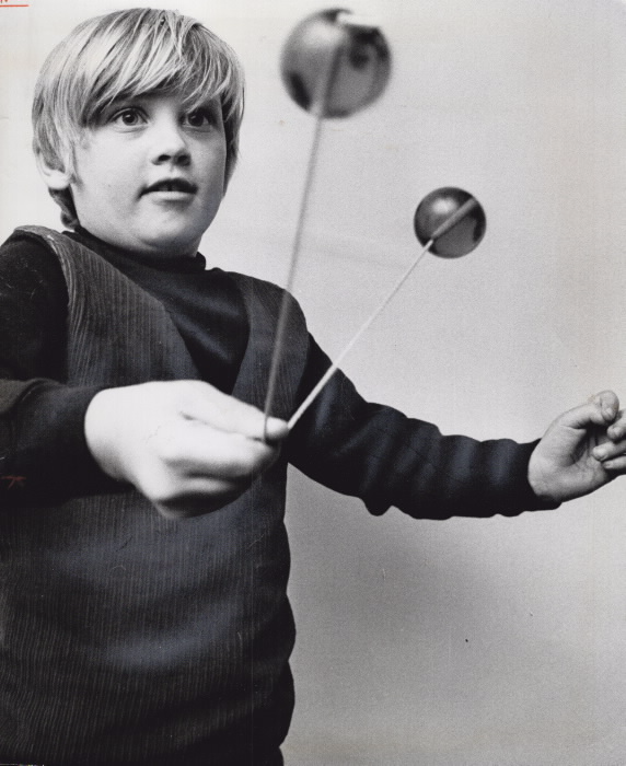 Boy plays with a toy that consists of two balls attached by string
