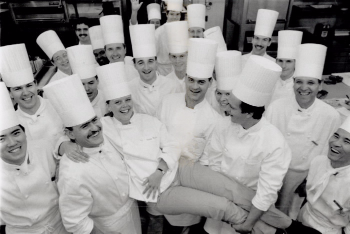 Susan Weaver being held up be other staff  all with chef hats