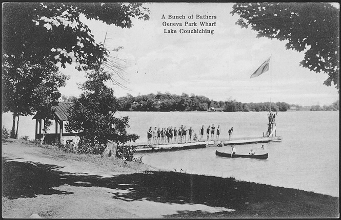 A dock on a lake with a group of swimmers.
